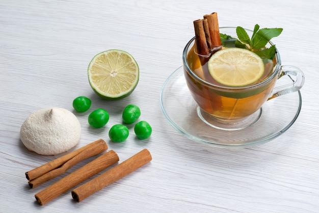 Eine tasse tee von oben mit zitronenplätzchen und zimt auf weißem tee-dessertbonbon