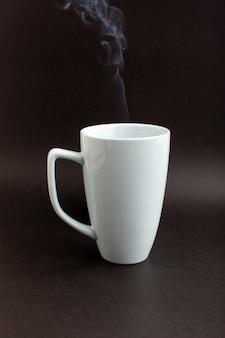Eine tasse tee von vorne in der weißen tasse auf dem dunklen schreibtisch trinkt heißen tee
