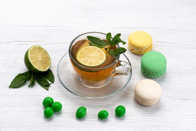 Eine tasse tee von vorne mit französischen macarons und zitrone auf weißem teekuchenkeks
