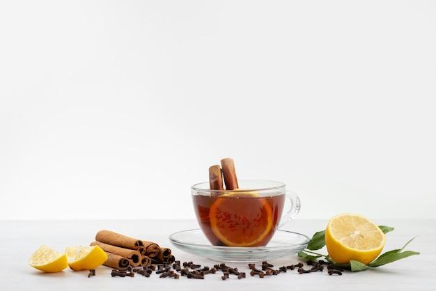 Eine tasse tee von vorne mit zitronenminze und zimt auf weißem tee-dessert-bonbon