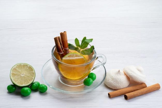 Eine tasse tee von vorne mit zitronenplätzchen und zimt auf weißen tee-dessert-süßigkeiten