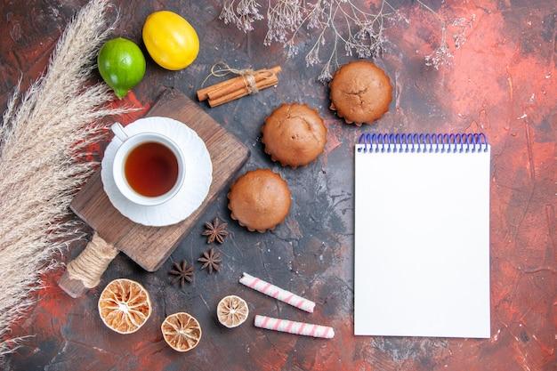 Eine tasse tee weißes notizbuch zitrusfrüchte süßigkeiten zimt eine tasse tee