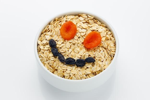 Eine tasse trockenes haferflockenmehl mit getrockneten früchten lächeln
