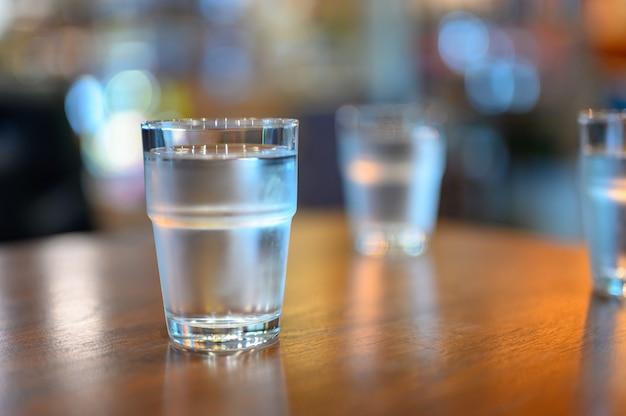 Eine tasse wasser auf dem holztisch bereit, zum getränk wegzunehmen.
