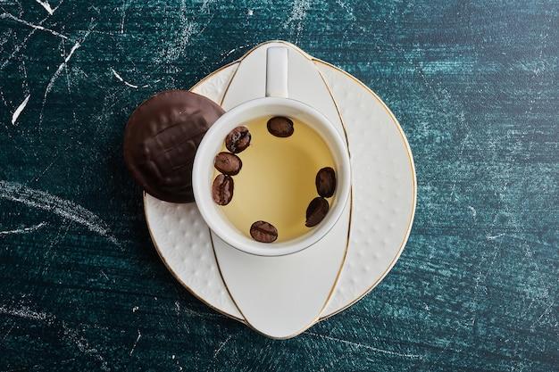 Eine tasse weißen kaffee mit bohnen und schokoladenkeksen.