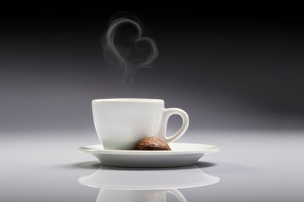Eine tasse weißen kaffees mit einem braunen keks und herzförmigem rauch in einem neutralen hintergrund