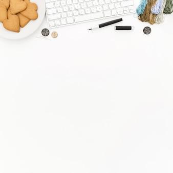 Eine tastatur, ein teller mit keksen, etwas faden und knöpfe auf einer weißen oberfläche