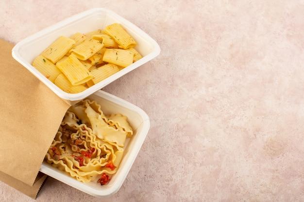 Eine teigmahlzeit von oben und italienische nudeln mit tomaten und fleisch in weißen schalen und paket auf rosa