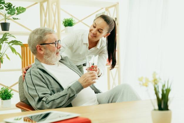 Eine tochter oder enkelin verbringt zeit mit dem großvater oder älteren mann, der wasser trinkt. familien- oder vatertag, emotionen und glück. lifestyle-porträt zu hause. mädchen, das sich um papa kümmert.