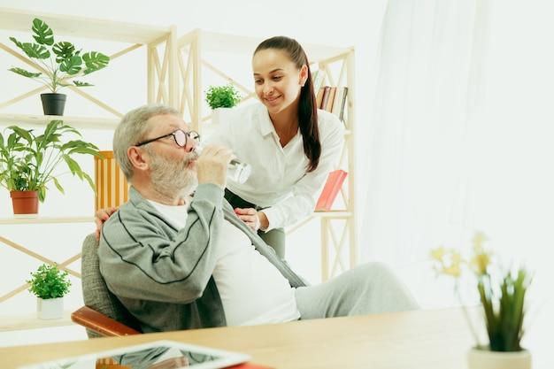 Eine tochter oder enkelin verbringt zeit mit dem großvater oder älteren mann, der wasser trinkt