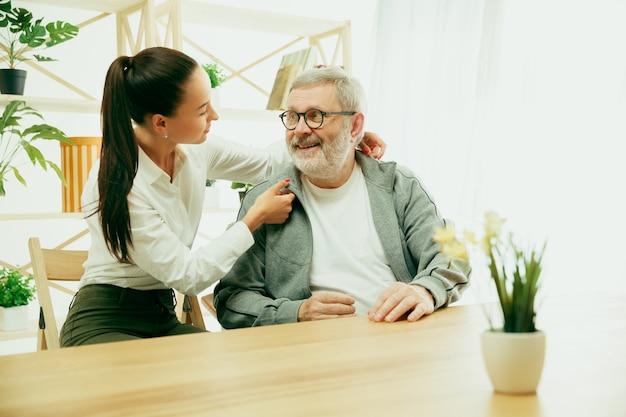 Eine tochter oder enkelin verbringt zeit mit dem großvater oder älteren mann. familien- oder vatertag, positive gefühle und glück. lifestyle-porträt zu hause. mädchen, das sich um papa kümmert.