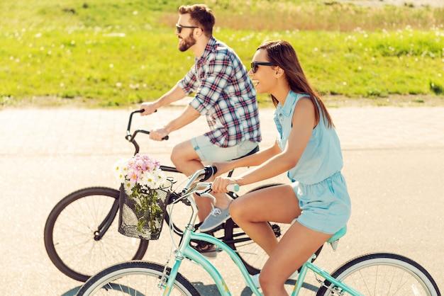 Eine tolle zeit zusammen haben. fröhliches junges paar, das zusammen fahrrad fährt und lächelt