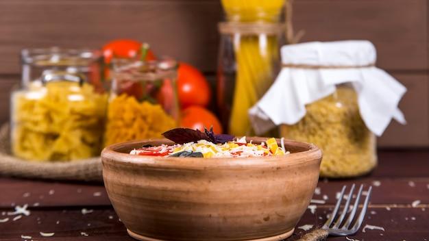 Eine tonplatte mit nudeln mit basilikum, tomaten und parmesan