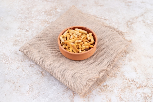 Eine tonschale mit grissini auf einem sack