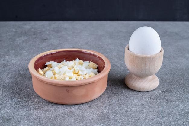 Eine tonschale mit leckerem salat und gekochtem ei. hochwertiges foto