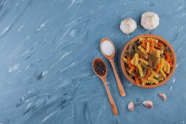 Eine tonschale mit mehrfarbigen rohen nudeln mit knoblauch auf einem blauen tisch.