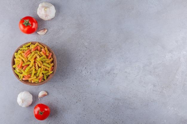 Eine tonschale mit mehrfarbigen rohen spiralnudeln mit knoblauch und frischen roten tomaten.