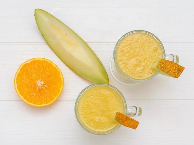 Eine tonschale mit melonenscheiben und zwei glasbechern mit smoothies auf einem tisch. der blick von oben. flach liegen.