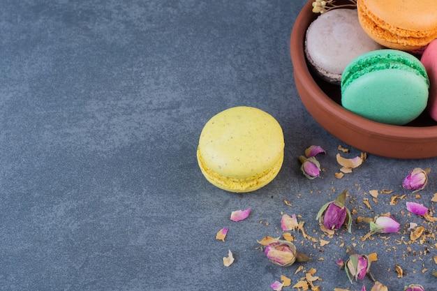 Eine tonschale voller makkaroni-kekse verschiedener farben auf einem dunkelgrauen hintergrund.