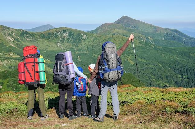Eine touristenfamilie mit großen rucksäcken blickt auf den höchsten berg der ukraine