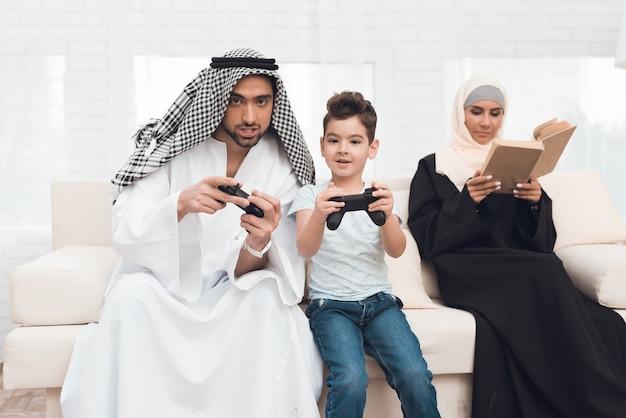 Eine traditionelle arabische familie spielt eine spielkonsole.