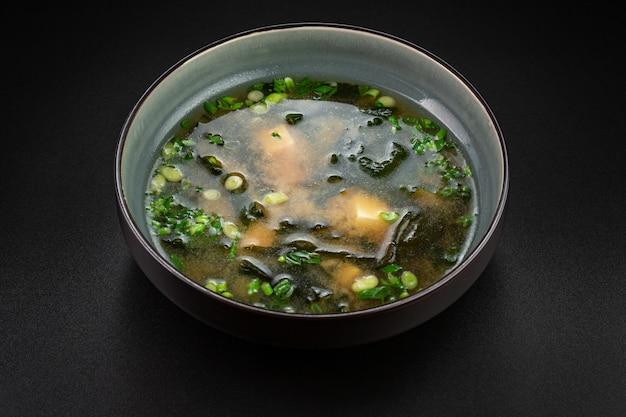 Eine traditionelle japanische suppe mit einer 2000-jährigen geschichte! die kombination aus wakame-seetang und tofu-käse mit frühlingszwiebeln und gewürzen.