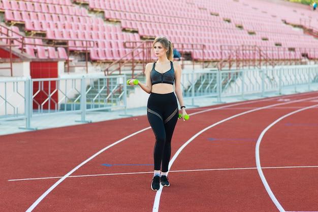 Eine trainerin mit dunklen haaren steht in einer sportuniform auf der roten laufbahn des stadions.