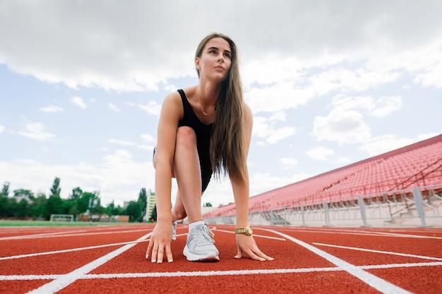 Eine trainerin mit dunklen haaren steht in sportuniform auf der roten laufbahn des stadions.