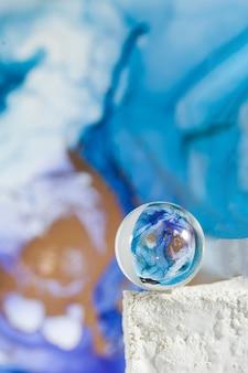 Eine transparente glaskugel auf einem abstrakten blauen hintergrund die technik der alkoholischen tinte