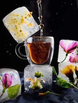 Eine transparente tasse tee in eis, eis in form von gefrorenen würfeln mit blumen