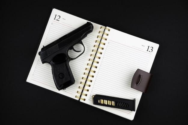 Eine traumatische pistole und munition liegen auf einem offenen notizbuch auf einer schwarzen oberfläche
