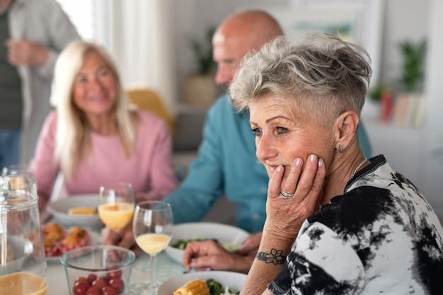 Eine traurige ältere frau mit freunden, die drinnen party machen und am tisch essen.