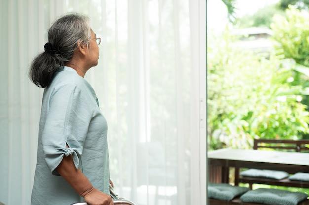 Eine traurige alte ältere frau benutzt eine gehhilfe, um vor fenstern zu stehen und nach draußen zu schauen und sich einsam zu fühlen