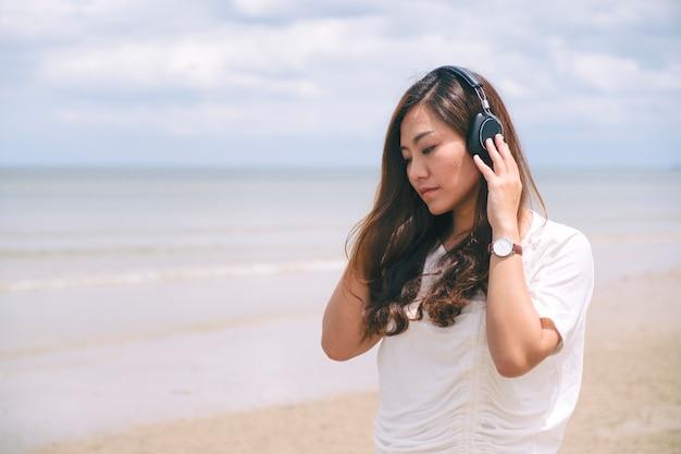 Eine traurige frau, die musik mit kopfhörer am meer hört