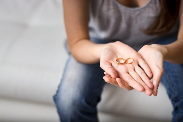 Eine traurige frau zu sein, schaut auf den ring in der handfläche vor ihm, nostalgisch über einen ehemaligen ehemann, eine familie, eine ehe. das konzept einer beziehung, scheidung.