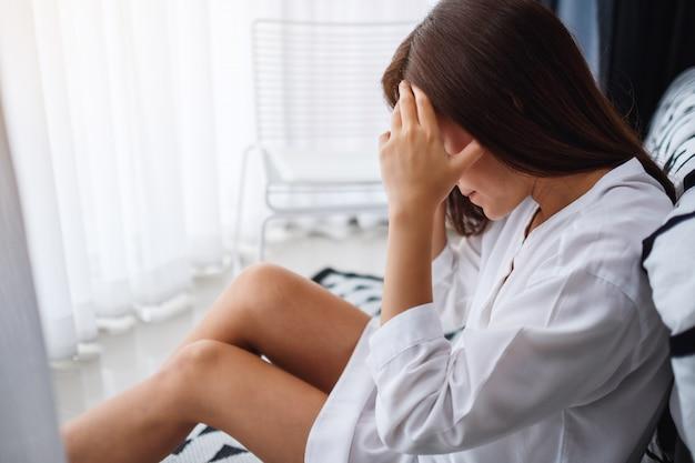 Eine traurige und gestresste junge asiatische frau, die allein im schlafzimmer sitzt
