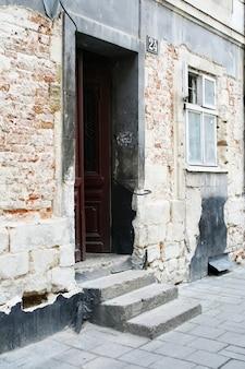 Eine treppe und eine offene tür, die zu einem alten backsteinhaus führen. neben der tür ist ein fenster