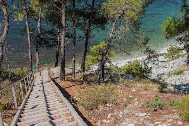 Eine treppe zum meer auf den felsen führt zu einem wilden strand.