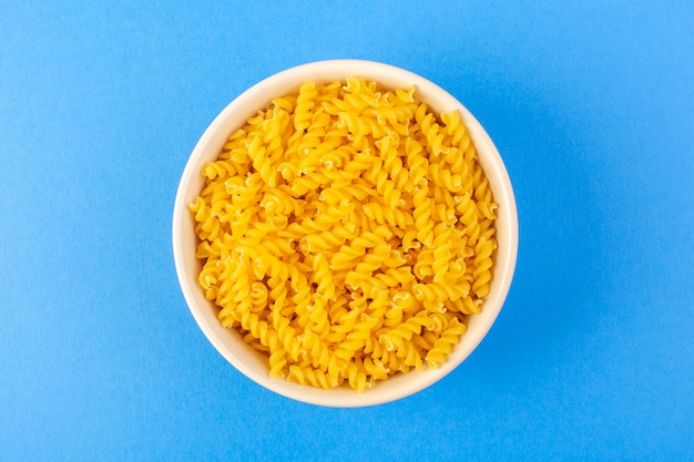 Eine trockene pasta von oben italien bildete kleine gelbe rohe pasta innerhalb der cremefarbenen runden schüssel, die auf dem italienischen hintergrund italienische spaghetti-nahrungsnudeln isoliert wurde