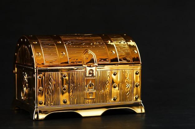 Eine truhe aus gold mit juwelen auf schwarzem grund. freiraum, das konzept des reichtums. zurückhaltend.