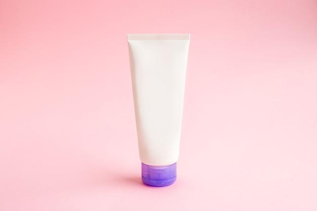 Eine tube sahne auf rosa hintergrundmodell. beauty spa medizinische hautpflege und kosmetische lotion creme verpackung produkt