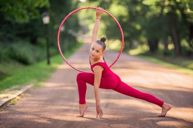 Eine turnerin in einem roten kommando macht an einem sommerabend eine übung mit einem reifen im park