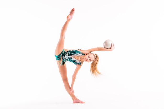 Eine turnerin in einem smaragdgrünen badeanzug führt eine übung mit einem ball auf einem weiß durch