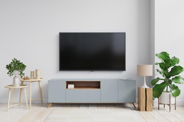 Eine tv-wand, die auf einem schrank in einem wohnzimmer mit einer weißen wand montiert ist. 3d-rendering