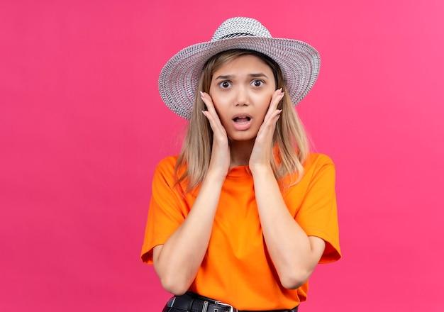 Eine überraschte hübsche junge frau in einem orangefarbenen t-shirt, das einen sonnenhut trägt, der hände auf gesicht hält, während er auf eine rosa wand schaut