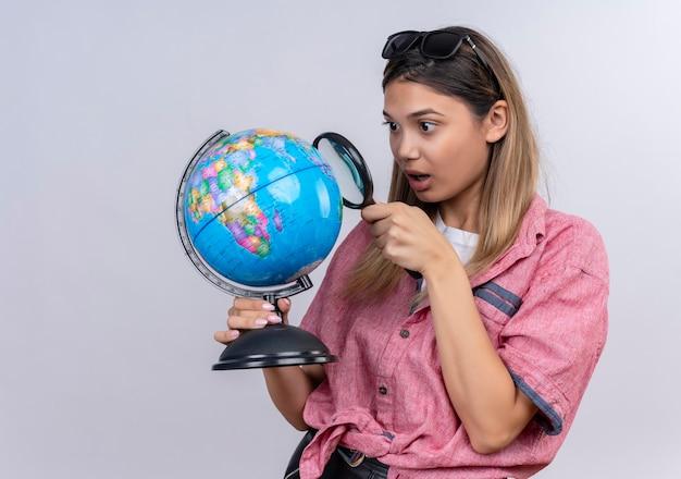 Eine überraschte junge frau, die rotes hemd in der sonnenbrille trägt, die einen globus hält, während sie ihn mit lupe betrachtet