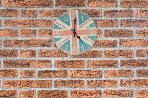 Eine uhr weinlese- und england-flagge für hintergrund nach innen auf backsteinmauerhintergrund