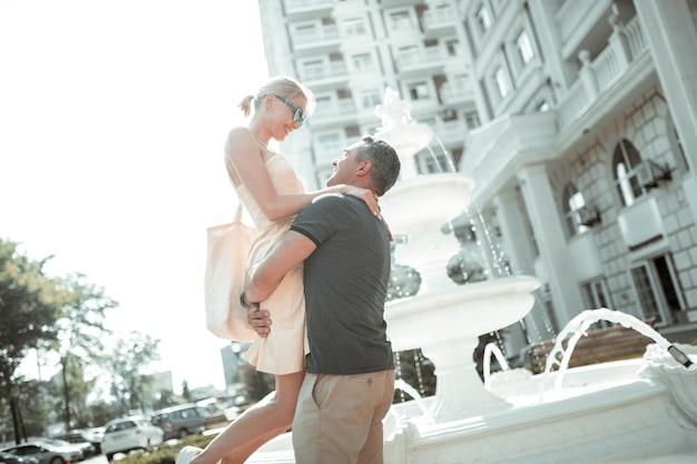 Eine umarmung geben. fröhliche blonde frau, die in den händen ihres starken fürsorglichen mannes in der stadtstraße lächelt.