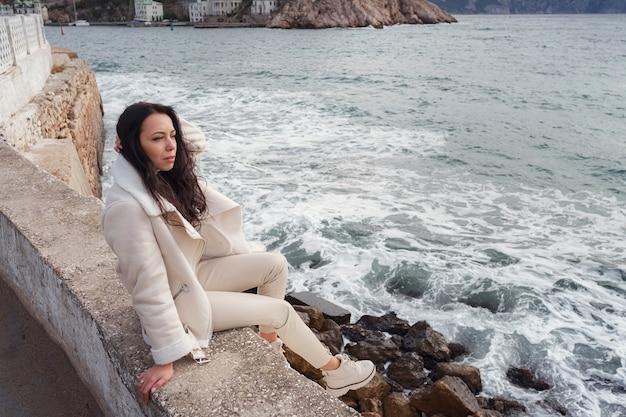 Eine unbeschwerte kaukasische frau in beigefarbener kleidung, die an einem warmen, windigen tag den blick auf das meer genießt.