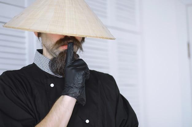 Eine urkomische parodie auf einen asiatischen mann in einem vietnamesischen hut mit bart. porträt. asiatischer café-koch.